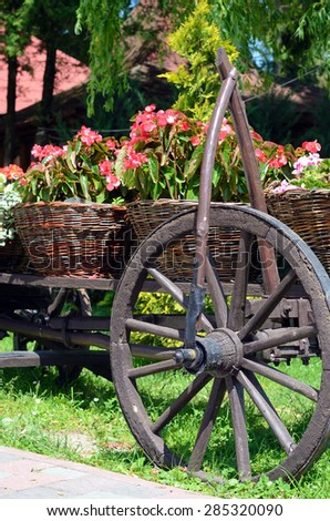 Baskets of flowers and wheel of ancient peasant cart on a sunny