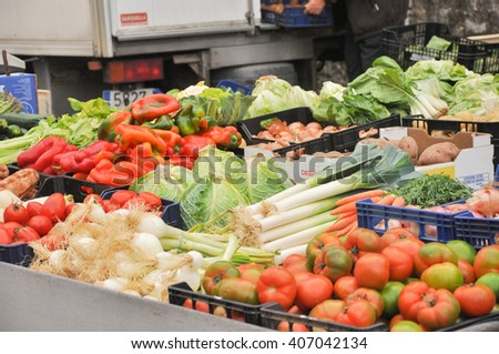 baskets of fruit and vegetables in the market with tomatoes, beans, artichokes - stock photo