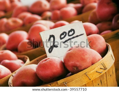 baskets of red-skinned potatoes for sale at the farmers market, focus on foreground - stock photo