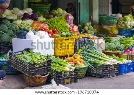Baskets of vegetables and fruits selling on the pavement of the street - stock photo