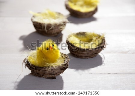 Baskets Or Nests With Yellow Feathers And Easter Chick In Sunny Light With Copy Space Free Text Or Your Text Here For Happy Easter Greetings Or Easter Decoration Close Up Or Macro Wooden Background - stock photo