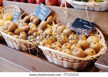 Baskets with fresh kiwi on street market display - stock photo