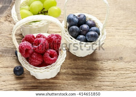 Baskets with fruits: raspberry, blueberry and grapes. Wooden background.  - stock photo