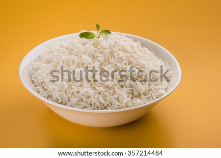 basmati rice in a brass bowl, cooked basmati rice, cooked plain rice, cooked white basmati rice, steamed basmati rice served in white bowl over yellow background - stock photo