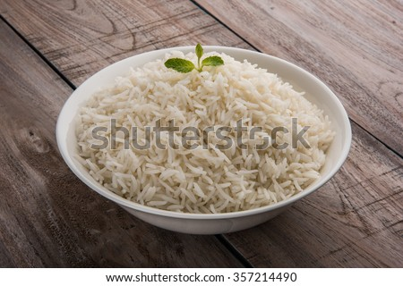 basmati rice in a brass bowl, cooked basmati rice, cooked plain rice, cooked white basmati rice, steamed basmati rice served in white bowl over wooden background - stock photo