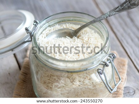Basmati rice in a glass jar with a spoon - stock photo