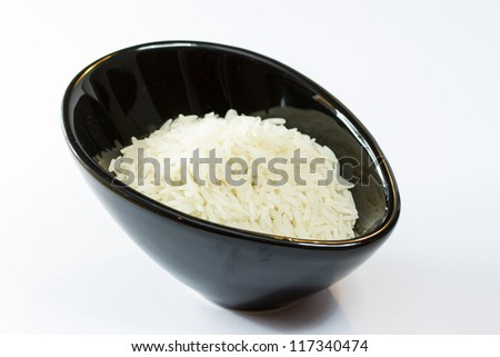 Basmati rice in black pot isolated on white background - stock photo