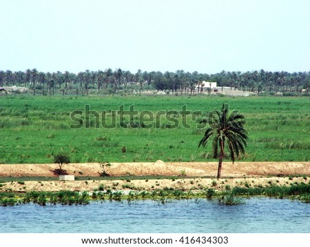 BASRA, IRAQ - CIRCA MAY 2007: Banks of the Shatt al-Arab, leading to the Tigris River, with fertile fields stretching out beyond it, seen from the wall of a US government camp