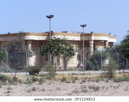 BASRA, IRAQ - CIRCA MAY 2007: Sadaam-era palace enclosed within a government camp, surrounded by chain link fence and with badly overgrown grounds