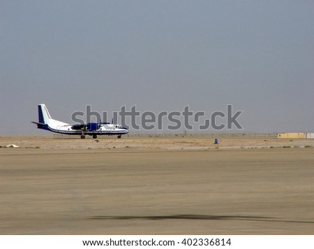 BASRA, IRAQ - MAY 10, 2007: Small charter aircraft landing at the commercial airport with only desert in the background