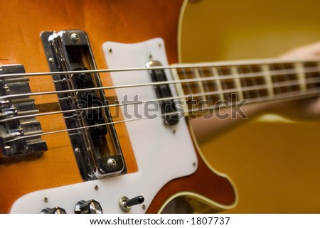 Bass guitar being held and ready to play. - stock photo