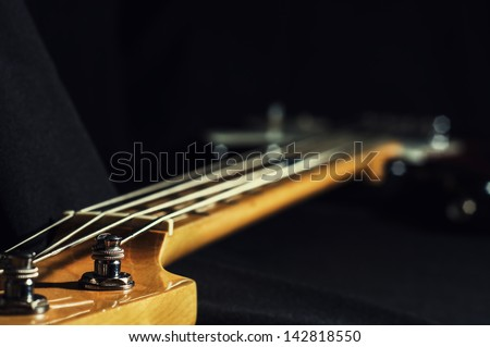 bass guitar. black background.close-up. - stock photo