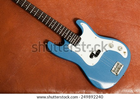 Bass Guitar on brown leather texture as vintage background. - stock photo