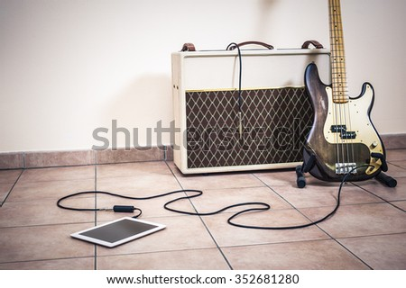 Bass guitar on digital tablet - stock photo