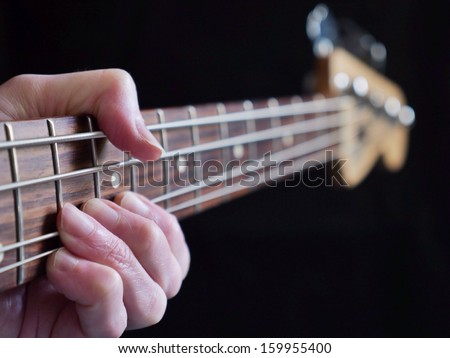 Bass guitar string-bending on black background. - stock photo