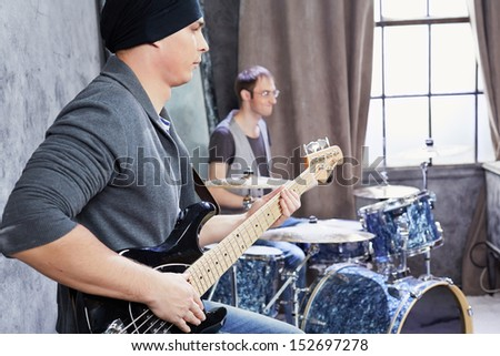 Bass guitarist and drummer play music - stock photo