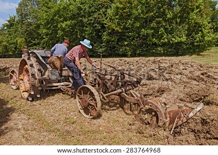"BASTIA,RA, ITALY - MAY 17: farmers recalling the old farm work plowing the field with an old tractor Landini during the country fair ""Sagra Paesana di Bastia"" on May 17, 2015 in Bastia, RA, Italy  - stock photo"