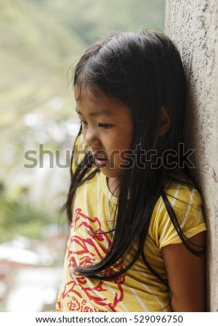Batad,Philippines-October 07,2016: Little cute girl plays in the door of his house on October 07, Batad,Philippines.