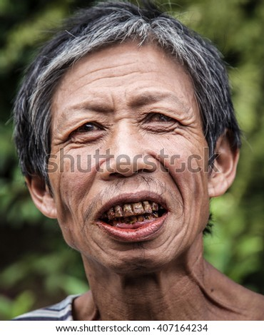 BATANGAS, PHILIPPINES - DECEMBER 10, 2015: An unidentified man of the Hanunoo Mangyan tribe of the Philippines smiles through betelnut stained teeth in Batangas, Philippines, in December 2015.