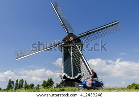 Batenburg, The Netherlands - May 27, 2012: Mill on a dike with a scotter in front.