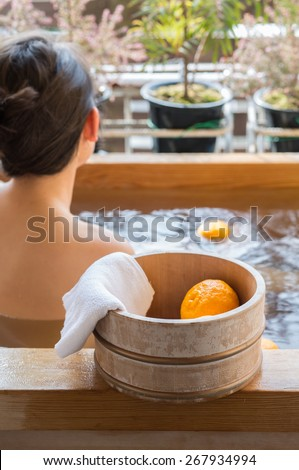 Bath bucket with fruits of yuzu during traditional bathing at Japanese onsen. This bath also known as yuzuyu and yuzuburo usually taken during winter solstice, custom that dates to early 18th century. - stock photo