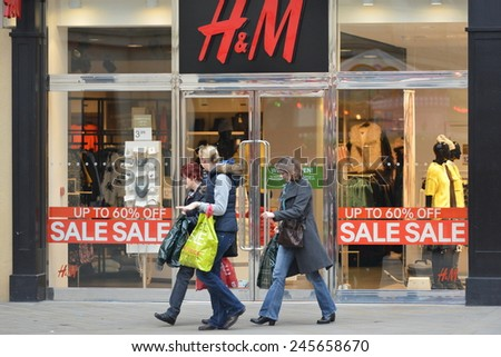 BATH - DEC 26: People walk past a H&M store in Southgate shopping district for the Boxing Day Sales on Dec 26, 2014 in Bath, UK. Many stores across the country traditionally hold sales on Boxing Day.  - stock photo
