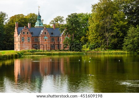 Bath House hunting lodge reflected on the lake water near Frederiksborg castle in Copenhagen, Denmark. Romantic park around lonely pond with water birds. - stock photo