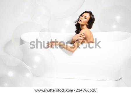Bath in the foam. Beautiful hispanic, latino  in a bathtub full of large bubbles  - stock photo