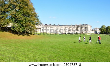 BATH - OCT 17: People gather in the warm sun in Victoria Park at the landmark Royal Crescent on Oct 17, 2010 in Bath, UK. Bath is a UNESCO World Heritage city with 4.5 million visitors a year. - stock photo