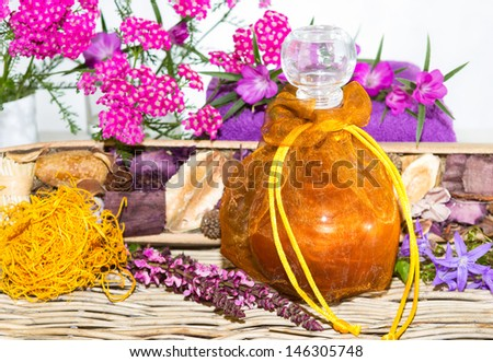 Bath oil or Essential oil with herbs and blossoms - stock photo