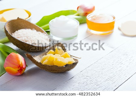 bath salt and bees wax on coconut shells, and cosmetic creams with soft sponges and tulips, white wood background