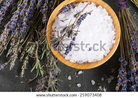 bath salt in bamboo bowl and dried lavender flowers on old black wood table, directly above - stock photo