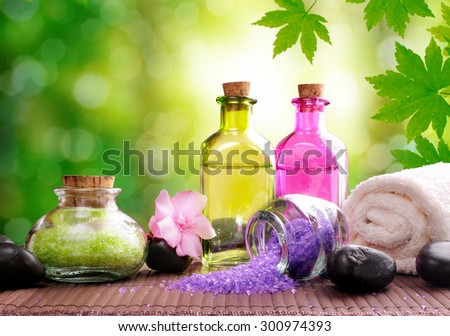 Bath salts and body oil on wood mat. Nature leaves and bokeh background. Horizontal composition