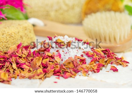 Bath salts covered in fragrant dried rose petals or floral potpourri with a bathing brush and sponge for pampering yourself at bath time - stock photo
