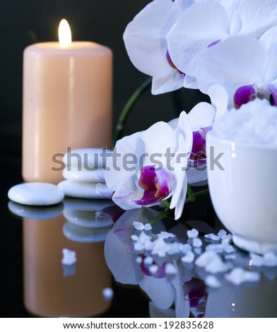 Bath sea salt with candle and orchid on the black background. - stock photo