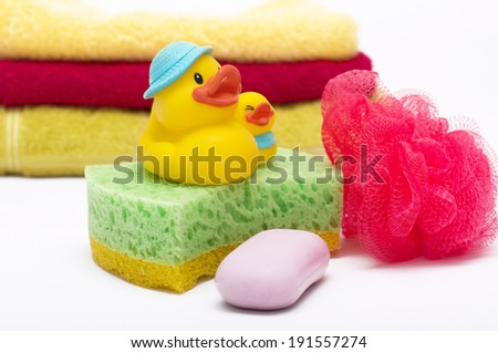 Bath sponge, towels and rubber duck on white background - stock photo