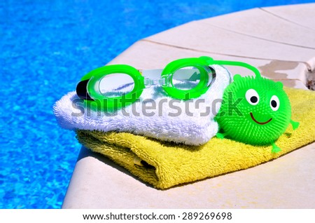 bath towels, goggles, toy against blue water in the swimming pool