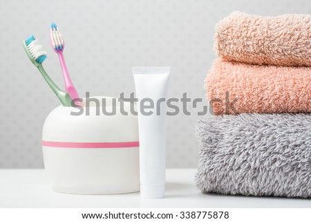 Bath towels of different colors, thoot brushes and toothpaste on light background - stock photo