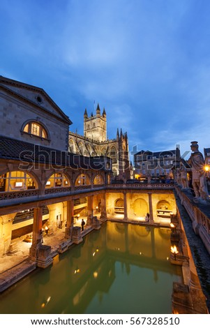 BATH, UK - AUGUST 25, 2011 : The Roman Baths and Bath Abbey at night. The Baths and Abbey are popular tourist attractions in the centre of the historic British city.