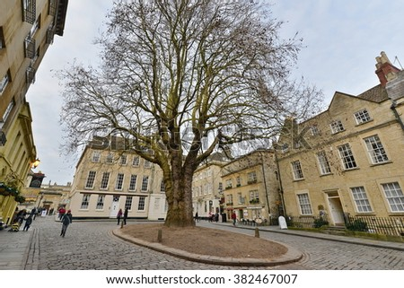 BATH, UK - FEB 16, 2016: People pass through Abbey Green and its landmark sycamore tree in the city centre. The famous Unesco World Heritage city in Somerset receives 4 million visitors each year.