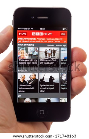 BATH, UK - JANUARY 16, 2014: A hand holding an Apple iPhone 4s displaying the front page of the BBC News App, against a white background. The app can be used to read the latest stories or watch video.