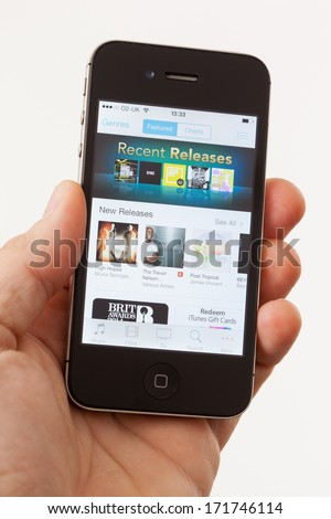 BATH, UK - JANUARY 15, 2014: A man's hand holding an Apple iPhone 4s which is displaying the front page of the Apple iTunes store. Shot in close-up against a plain background. - stock photo