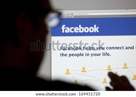 BATH, UK - MAY 4, 2011: Close-up of the Facebook homepage displayed on a LCD computer screen with silhouette of a man's head and hand out of focus in the foreground. - stock photo