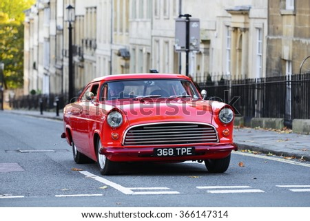 BATH, UK - OCT 18, 2014: A motorist drives a highly modified classic muscle car on a city centre road. - stock photo