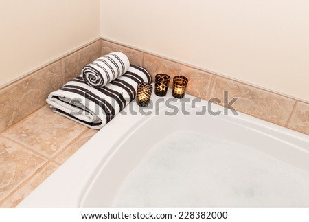 Bath with foam, fresh folded towels and candle lights. - stock photo