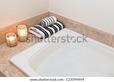 Bath with foam, fresh folded towels and cozy lanterns. - stock photo