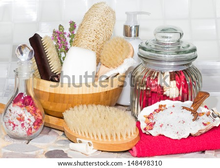 Bathing accessories for a luxury spa treatment with body brushes, soaps, marine bath salts and scented dried rose petals - stock photo