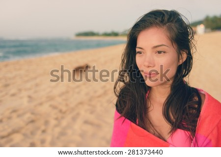 Bathing beach woman with towel relaxing portrait. Young pretty biracial Asian Caucasian girl wrapped in towel standing in beach sunset. Female enjoying summer holiday travel vacation. Hawaii. - stock photo