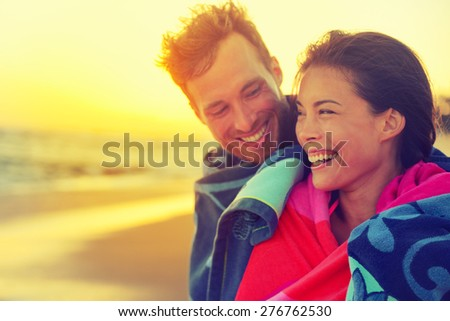 Bathing romantic couple with towel on beach sunset. Portrait of happy young interracial couple embracing each other having fun outdoors during holidays vacation travel. Asian woman, Caucasian man. - stock photo