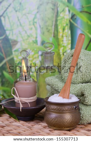 Bathing salt and massage oils with a stack of towels